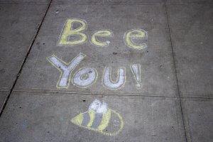Sidewalk chalk reading 'bee you'